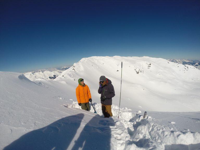 Schneeprofil wird im Gelände von Snowboardern gegraben