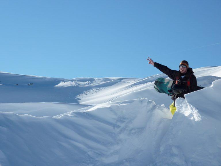 Snowboarder hat im Tiefschnee Spaß im Gelände