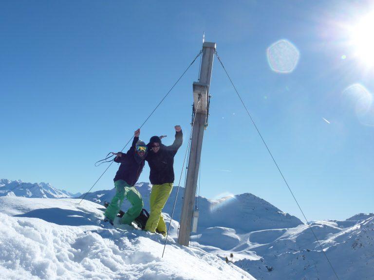 Panorama Foto von Snowboardern am Gipfel im Gelände